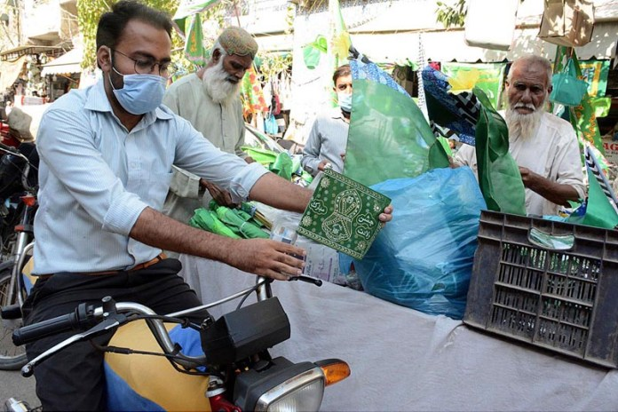KARACHI: October 22 – A motorcyclist fixes a flag after purchasing from a stall ahead of the Eid-e-Milad-un-Nabi. APP photo M. Saeed Qureshi