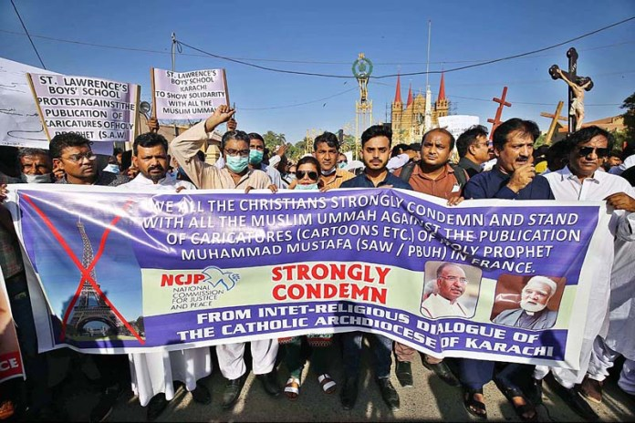 KARACHI: October 28 - Christian community holding protest demonstration against French government regarding the publication of blasphemous caricatures in French newspaper in front of St Patrick's Church. APP Photo by M Saeed Qureshi