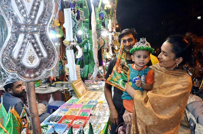 KARACHI: October 21 - A family purchasing flags and other stuff from vendor for upcoming Eid-e-Milad-un-Nabi (SAWW) celebrations. APP photo Syed Abbas Mehdi