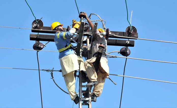 WAPDA staffers removing the faults of electric wires on a pole