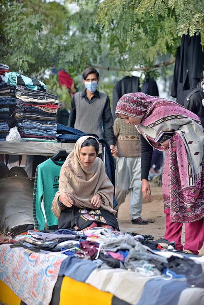 ISLAMABAD: November 22 – Women selecting and purchasing old warm clothes from vendor at Sunday Bazaar