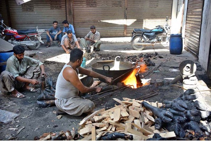 FAISALABAD: Vendor busy in roasting the feet of animals at Jhang Bazaar. APP photo by Tasawar Abbas