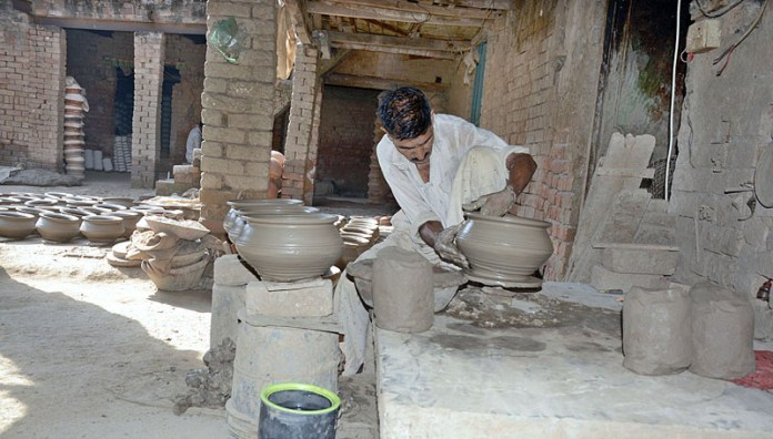 LAHORE: November 07 – A labourer giving final touches clay-made pot at his workplace. APP photo by Ashraf Ch