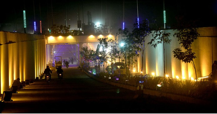 A view of newly constructed Firdous Market Underpass decorated with colourful lights on final stages of completion