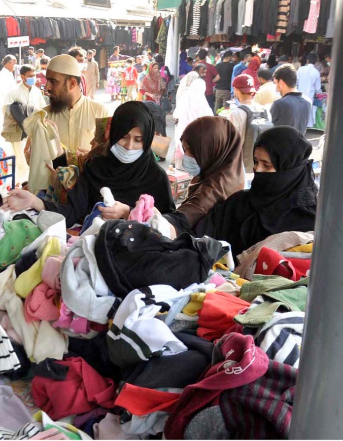 ISLAMABAD: November 01 - Women selecting and purchasing old warm clothes displayed by vendors at Sunday Bazaar as winter season approaching. APP photo by Saleem Rana
