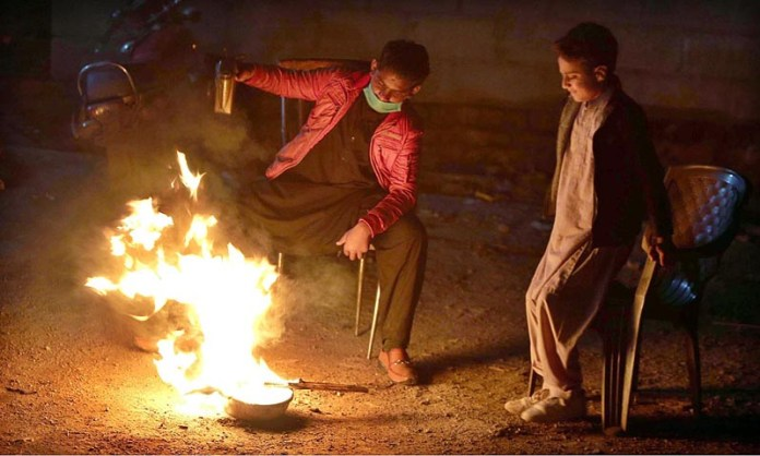 Youngsters sitting around fire at Dhoke Khabba to warm themselves during a cold weather