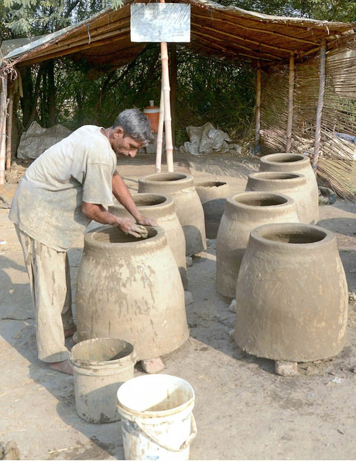 A worker preparing traditional ovens tandoor at his workplace