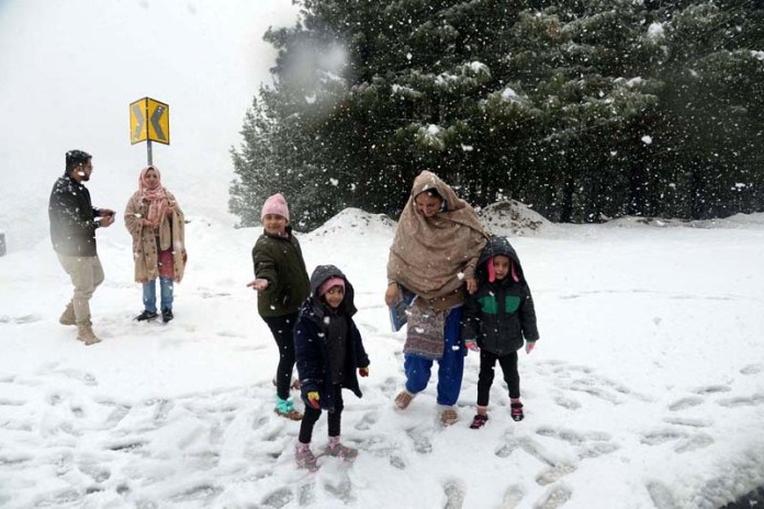 A family enjoying while playing on snow-covered road in Kaghan area during heavy snowfall