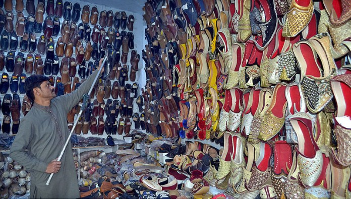 A shopkeeper arranging and displaying footwear to attract the customer in his shop
