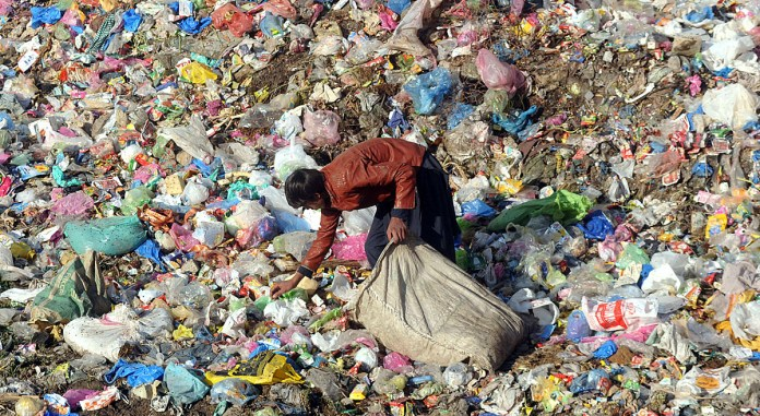 A gypsy youngster searching and collecting valuables from heap of garbage