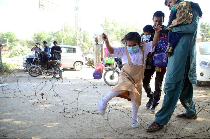 Children crossing barbed wire due to closed Red Crescent Road at Latifabad Unit Number 06 during smart lockdown after several cases of COVID-19 in different areas of Taluka Latifabad