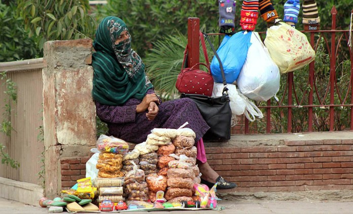 MULTAN: November 14 - A female vendor waiting for customers to sell different items at her roadside setup. APP photo by Tanveer Bukhari