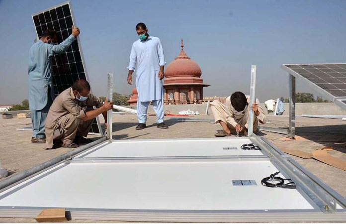 PESHAWAR: November 03 – Workers busy in installing solar panels on rooftop of Peshawar Museum. APP Photo by Shaheryar Anjum