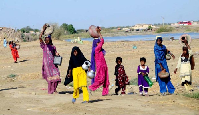 Woman along with children on the way while carrying pots on their head for filling drinking water at T.M Khan Road