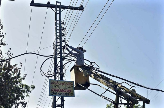 WAPDA staffer busy in repairing electric wire on electric pole