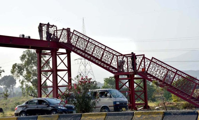 ISLAMABAD: November 03 - Workers busy in installing Pedestrians Bridge near Malpur Murree Road. APP photo by Irshad Sheikh