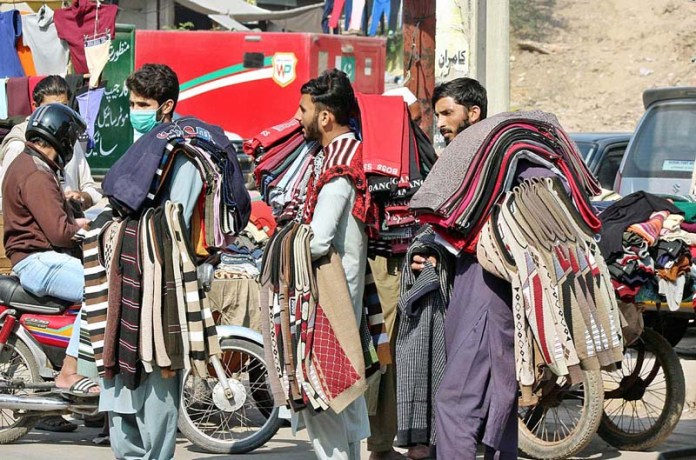 Vendors selling sweaters while shuttling in a local market