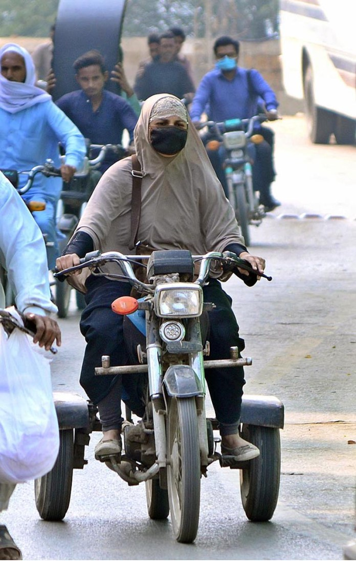 A disable woman wearing protective face mask for precautionary measures to protect from corona virus on the way on his special bike at Hilltop Road
