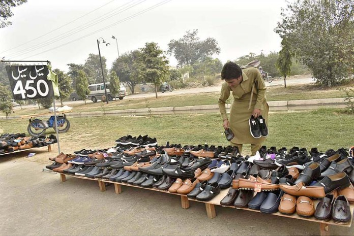 FAISALABAD: November 10 - A vender displaying and arranging shoes to attract the customers at his roadside setup at Rajbah Road. APP photo by Muhammad Waseem