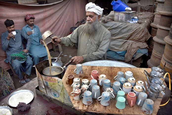 A vendor preparing tea in a traditional way for the customers on the roadside setup
