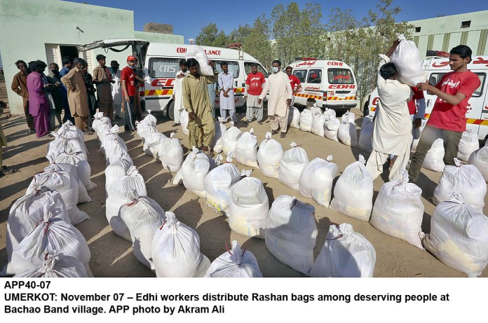 UMERKOT: November 07 – Edhi workers distribute Rashan bags among deserving people at Bachao Band village. APP photo by Akram Ali