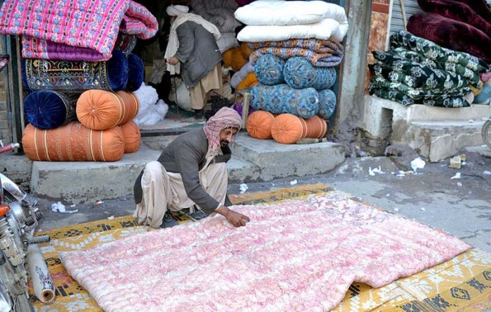A vendor preparing quilts for displaying outside his shop to attract the customers