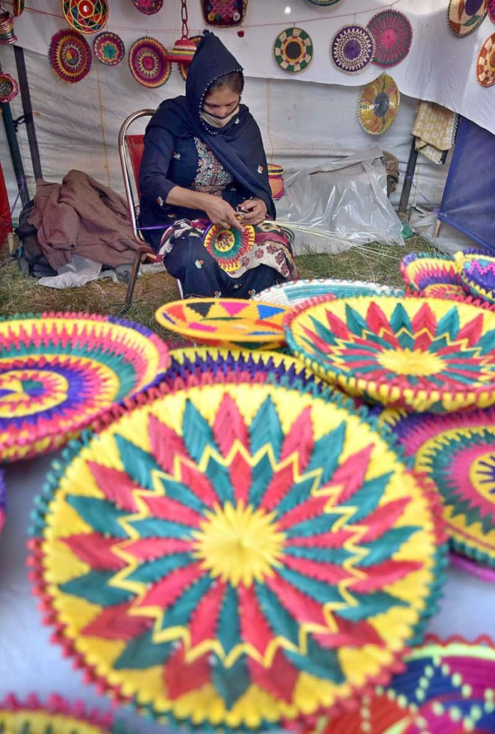 "ISLAMABAD: November 07 – An artisan at work at a stall during Folk Festival of Pakistan ""LOK MELA"" at Lok Virsa Shakarparian. APP photo by Irfan Mahmood"