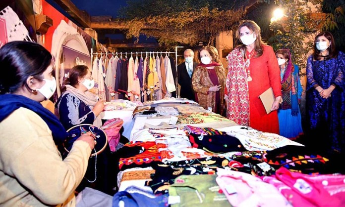 Begum Samina Arif Alvi viewing the stalls of embroidered dresses at the opening ceremony of fashion design show
