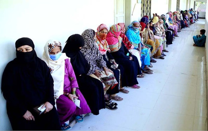 Deserving women waiting for their turn to receive cash under Ehsaas Cash Program at APWA Government Girls High School