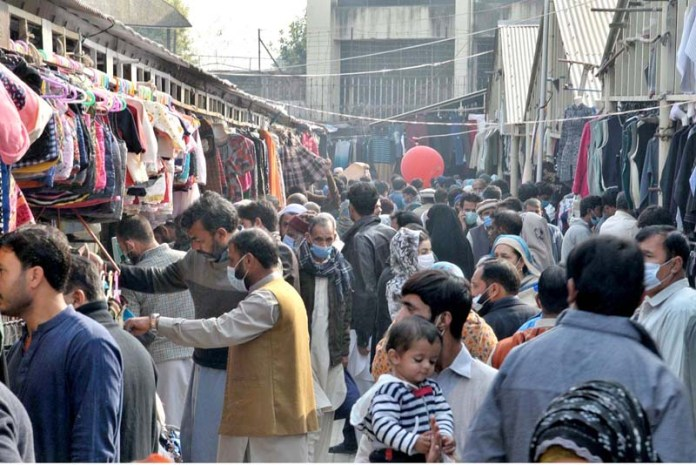 A large number of people, without following COVID-19 SOPs, selecting & purchasing second hand warm clothes from vendor at Weekly Sunday Bazar Aapbara