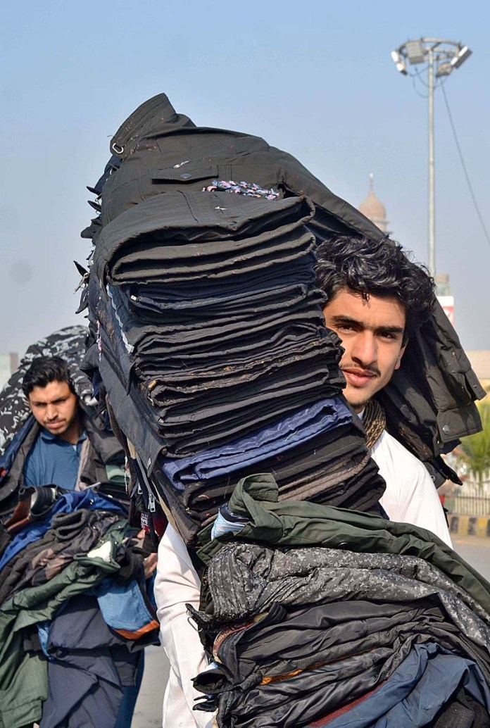 A vendor displaying jackets to attract the customers while shuttling on the road