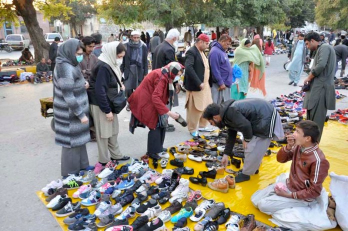 People busy in selecting and purchasing second hand shoes displayed by vendors at Aabpara Market