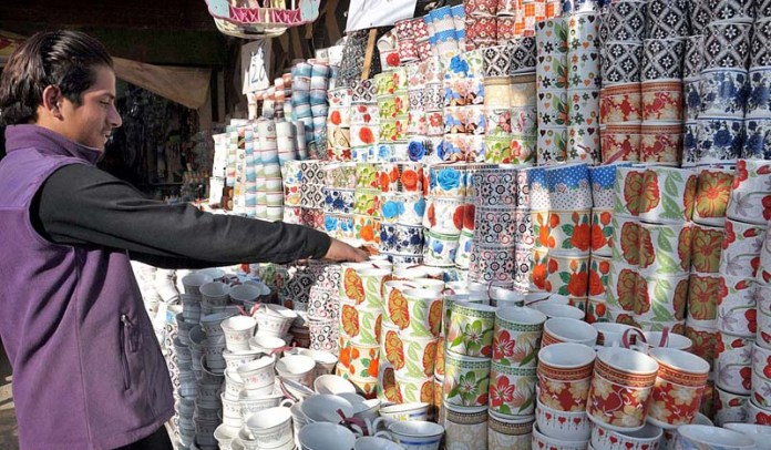 A vendor displaying and arranging tea cups to attract the customers at his shop