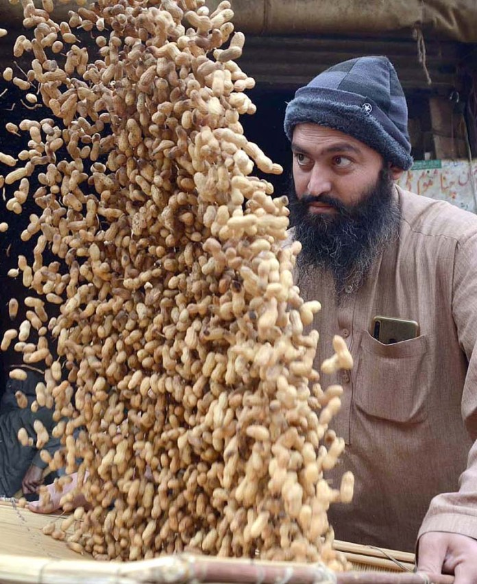 A labourer cleaning peanuts in a traditional way in Fridour Market
