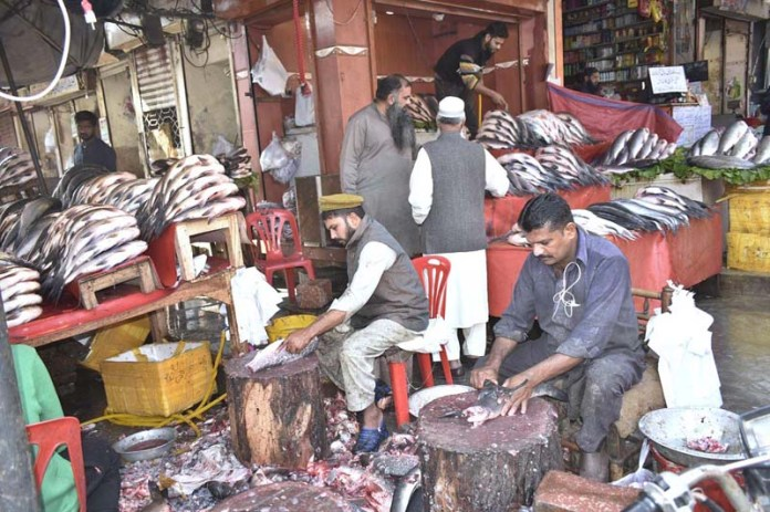 Shopkeepers busy in cutting fishes to sell them to the customers at Jhang Bazaar as fish is at high demand during winter due to increase in cold