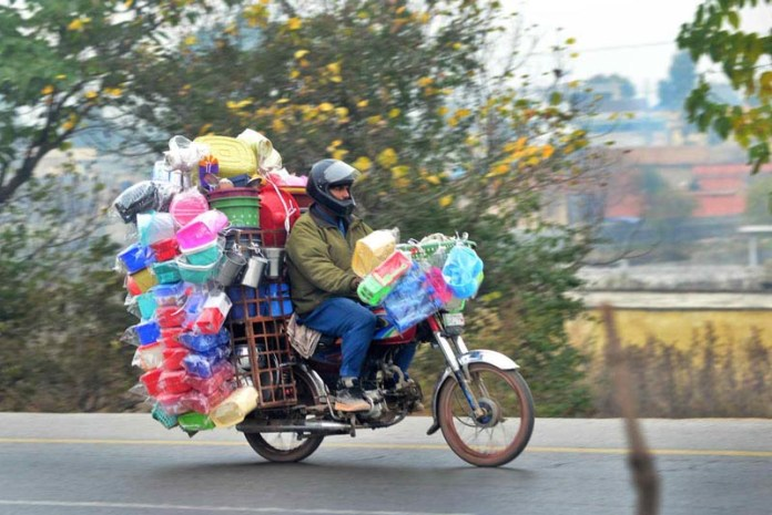 A street vendor on the way on motorcycle loaded with household stuff to attract the customers
