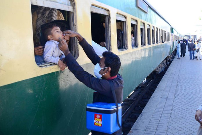 Health worker administering polio drop to children in the train during an anti-polio campaign at Railway Station