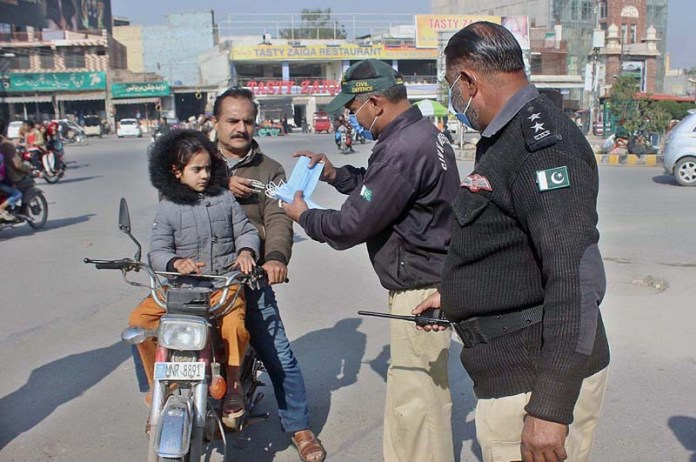 Civil Defence officials distributing face mask among the motorcyclists at Ghanta Ghar Chowk