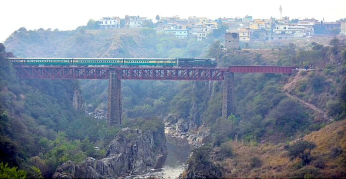 An attractive view of passenger train passing through a bridge near Sihalla