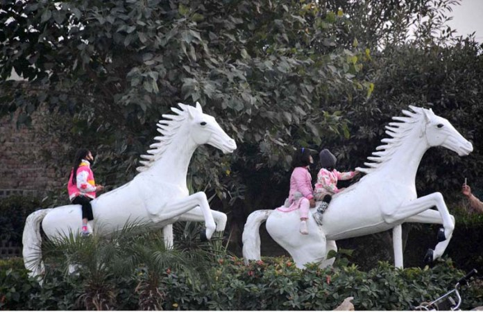 Children playing on a horse statue installed along Canal Road