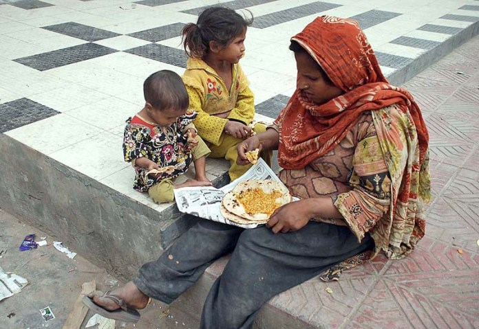 A female bagger with her children eating food while sitting near Shaheen Chowk