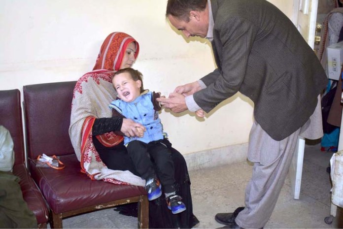 Doctor giving measles injection to child at DHQ Hospital Gilgit
