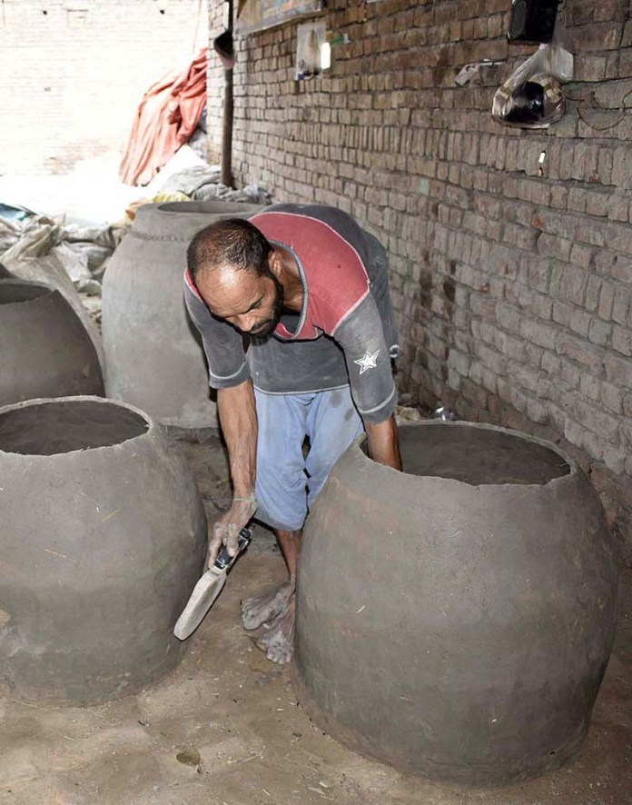 A worker preparing traditional clay-oven (Tandoor) at his workplace