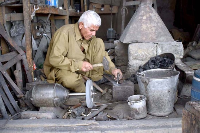 A blacksmith is preparing wood cutter for winter session