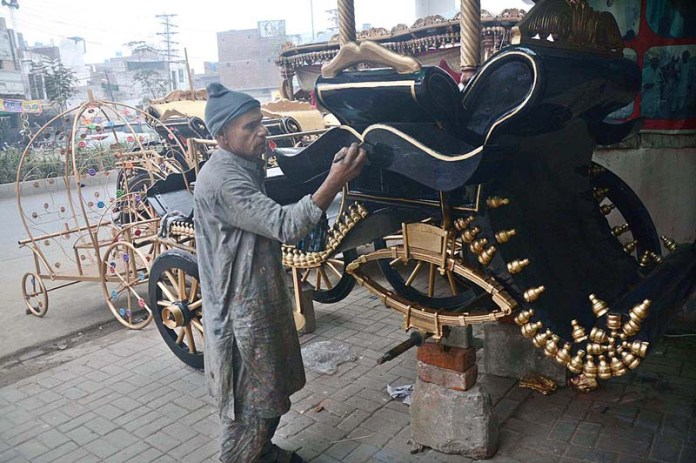 A painter busy in giving final touch to traditional horse cart at his workplace