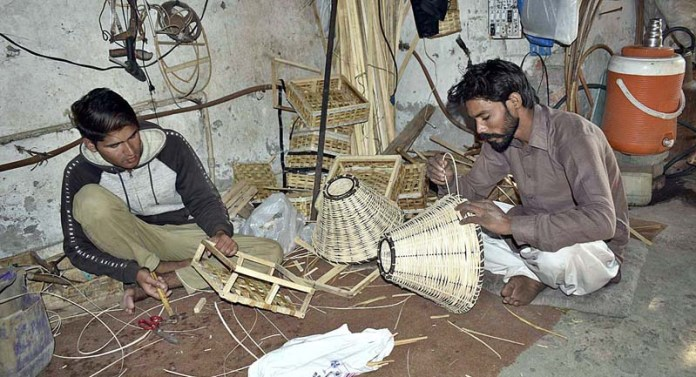 Workers preparing baskets with tree branches at their workplace