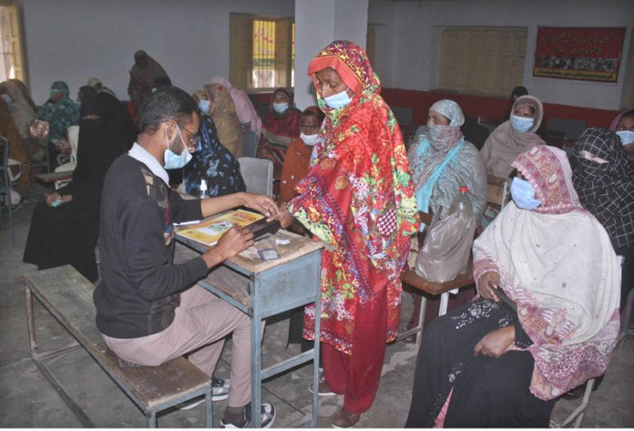 A woman passing through biometric identification process to get financial assistance under Ehsas Kafalat Program Phase-2 at Islamia Boys High School Daulat Gate