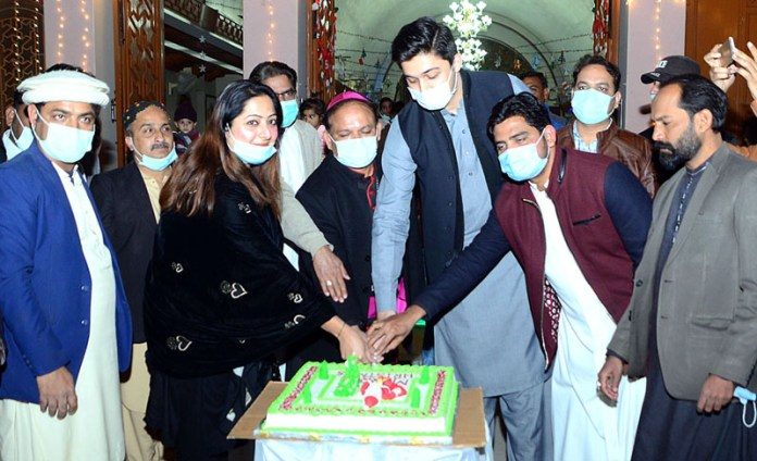 PTI Ladies Wing President Nazi Fatima with Christian community cutting the cake at St. Francis Xavier Church in connection with Christmas celebrations