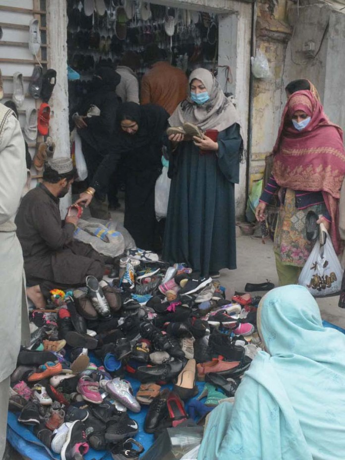 Ladies selecting and purchasing shoes from vendor at Liaquat Market