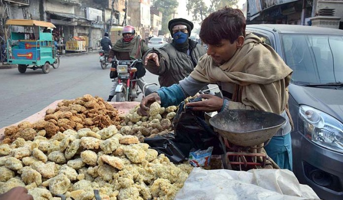A vendor displaying and arranging traditional sweet stuff (Gur) to attract the customers at his roadside setup